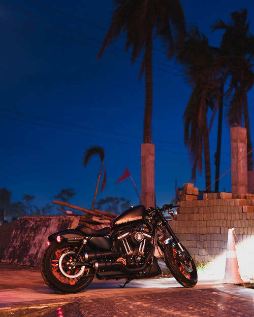 Photo of Black Motorcycle Parking Near Cinder Blocks at Night