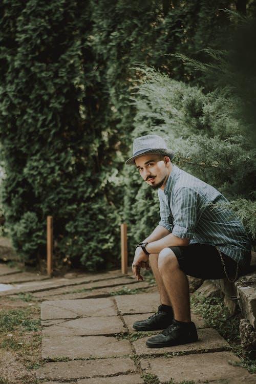 Photo Of Man Sitting Near Bushes