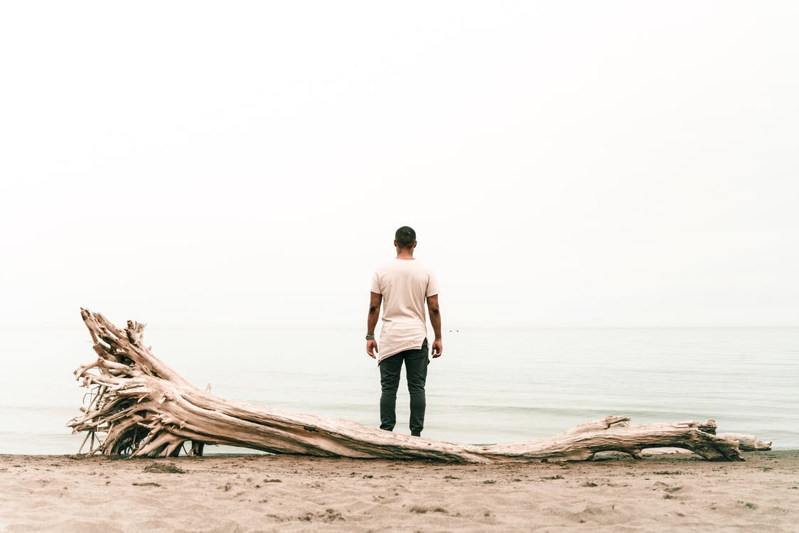 Back view Photo of Man Standing Beside Body of Water