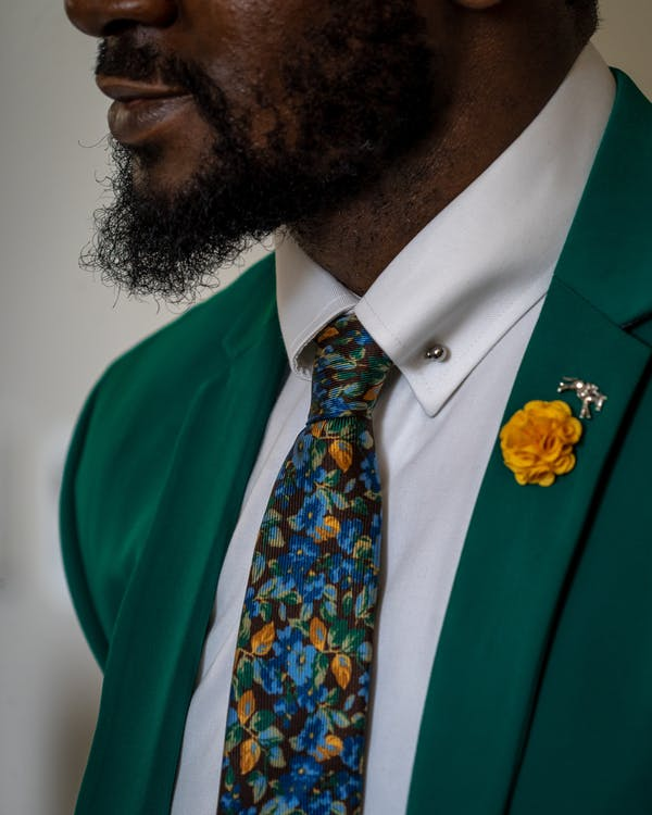 Person In Green Blazer, White Collared Top And Floral Necktie