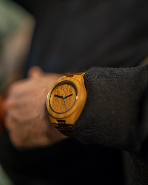 Selective Focus Photography of Person Wearing Round Brown Analog Watch