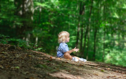 Side View Photo of Boy Sitting on the Ground Alone in the Forest