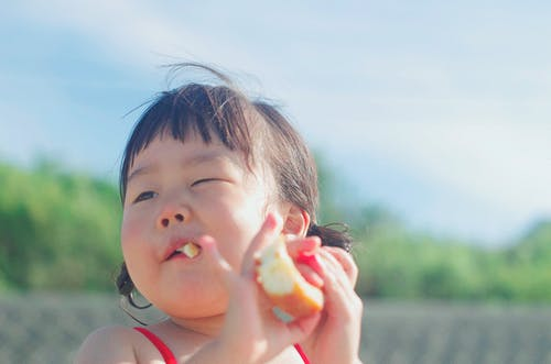 Close-up Photography Of A Girl Eating Bread