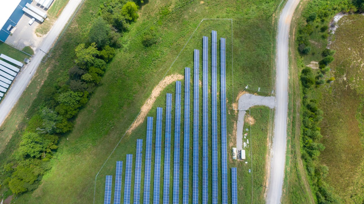 Aerial View of Solar Panels Array on Green Grass