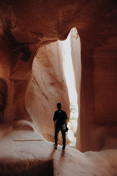 Photo Of Person Standing Inside Canyon Rocks