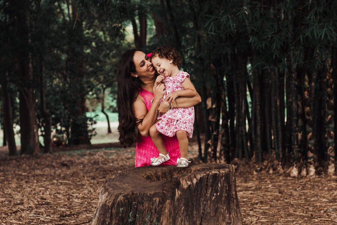 Photo Of Mother Holding Her Child