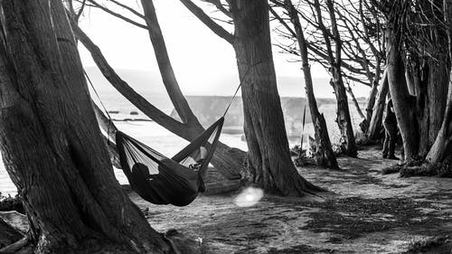Person Lying on Hammock in Greyscale Photography