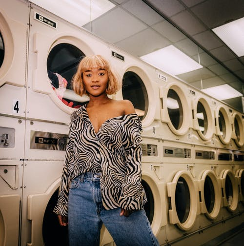 Photo of Woman Standing In Front of Washing Machines at Laundromat