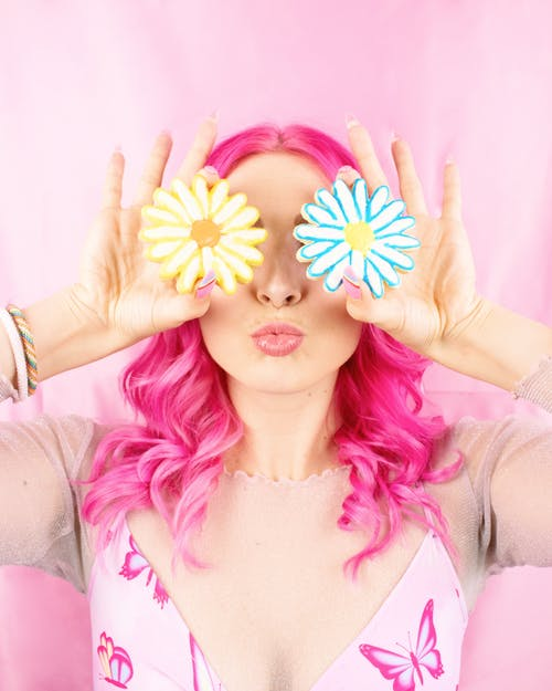 Woman with Pink Hair holding Flower Cookies