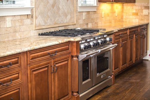 Gray Gas Range Between Brown Wooden Cabinet