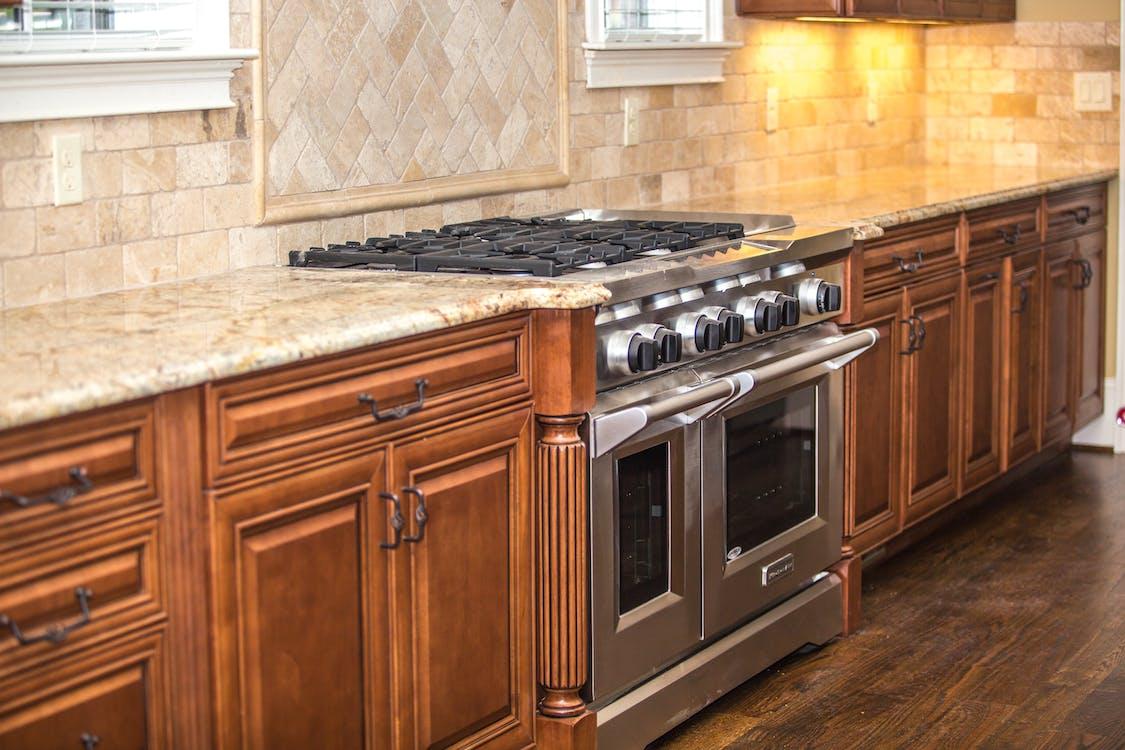 Gray Gas Range Between Brown Wooden Cabinet