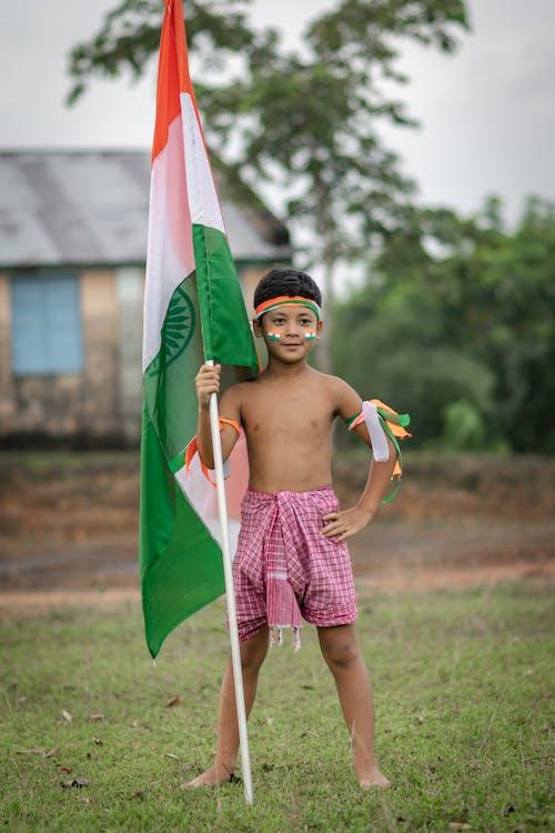 インドの旗を持っている少年