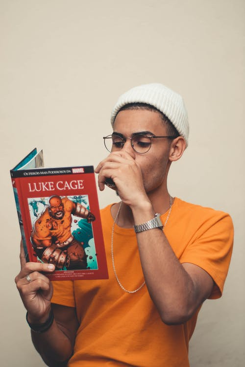 Man Wearing Yellow Shirt Reading Luke Cage Book