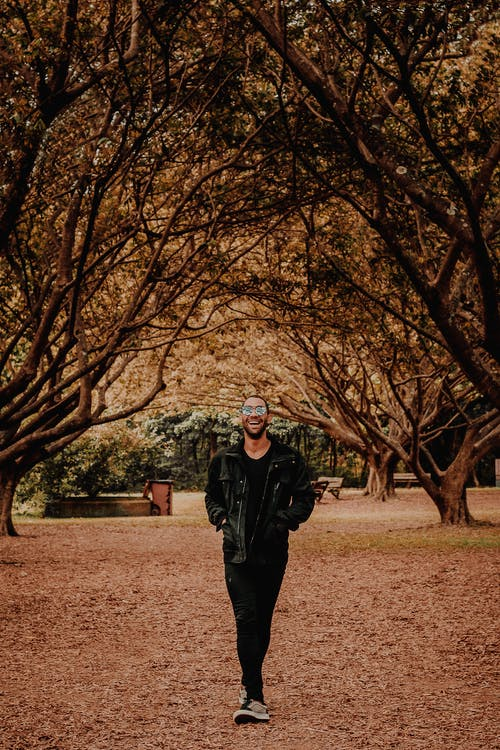 Photo Of Man Walking Under Trees