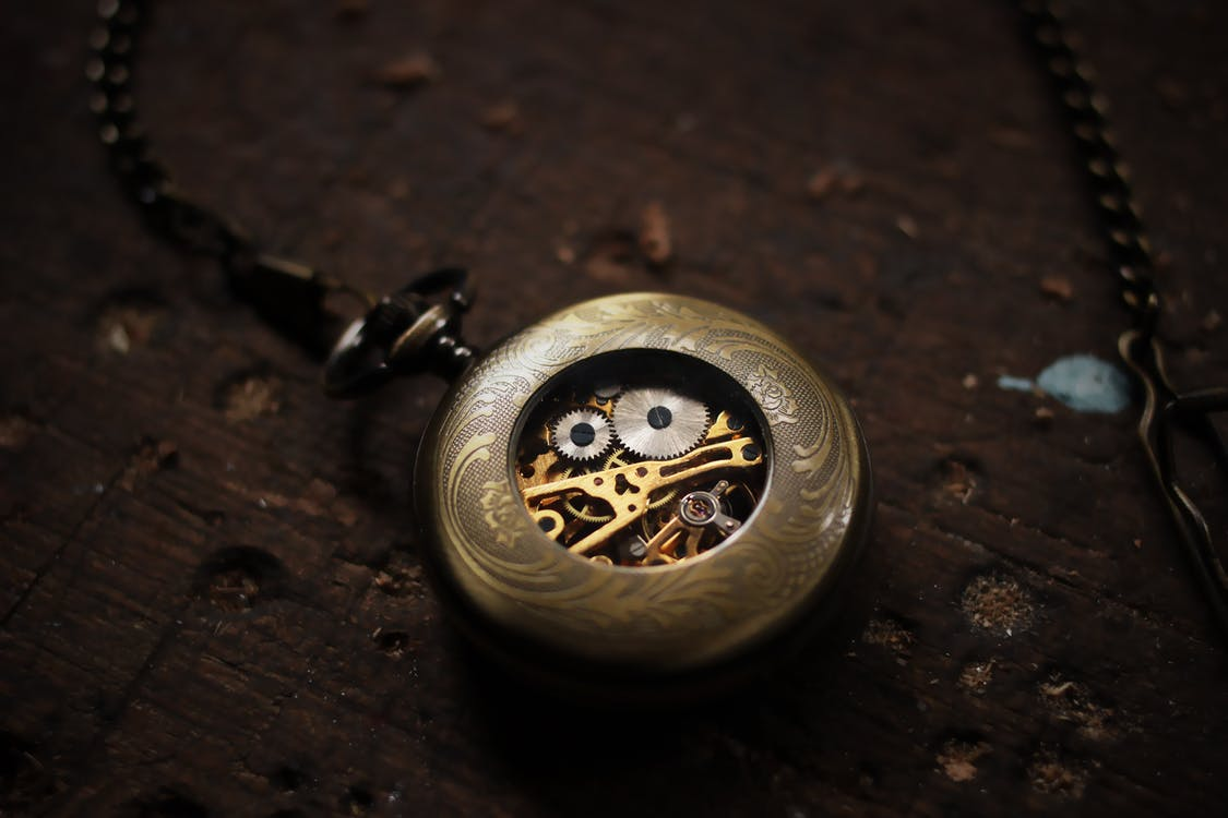 Silver-colored Pocket Watch on Brown Wooden Surface