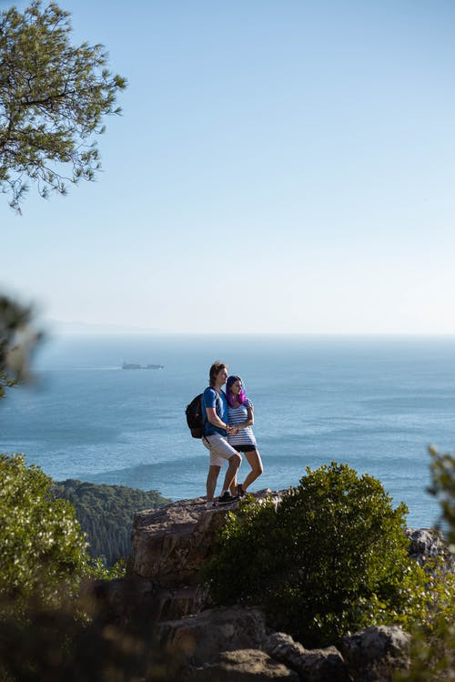 Man and Woman Standing on Cliff