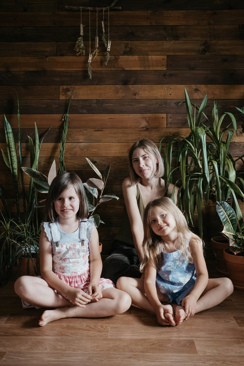 Three Girls Sitting Beside Green Indoor Plants