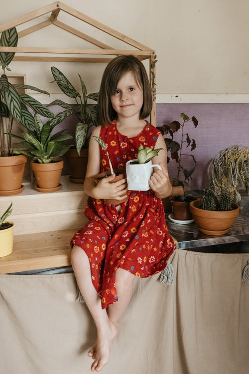Girl Sits on Shelf Holding Planter