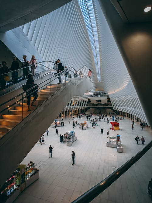 People on Escalator Inside White Building