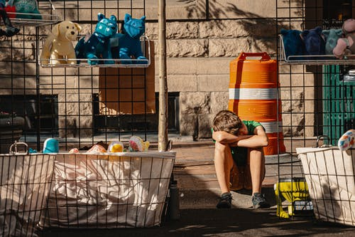 Boy Sits on Pavement Near Toys