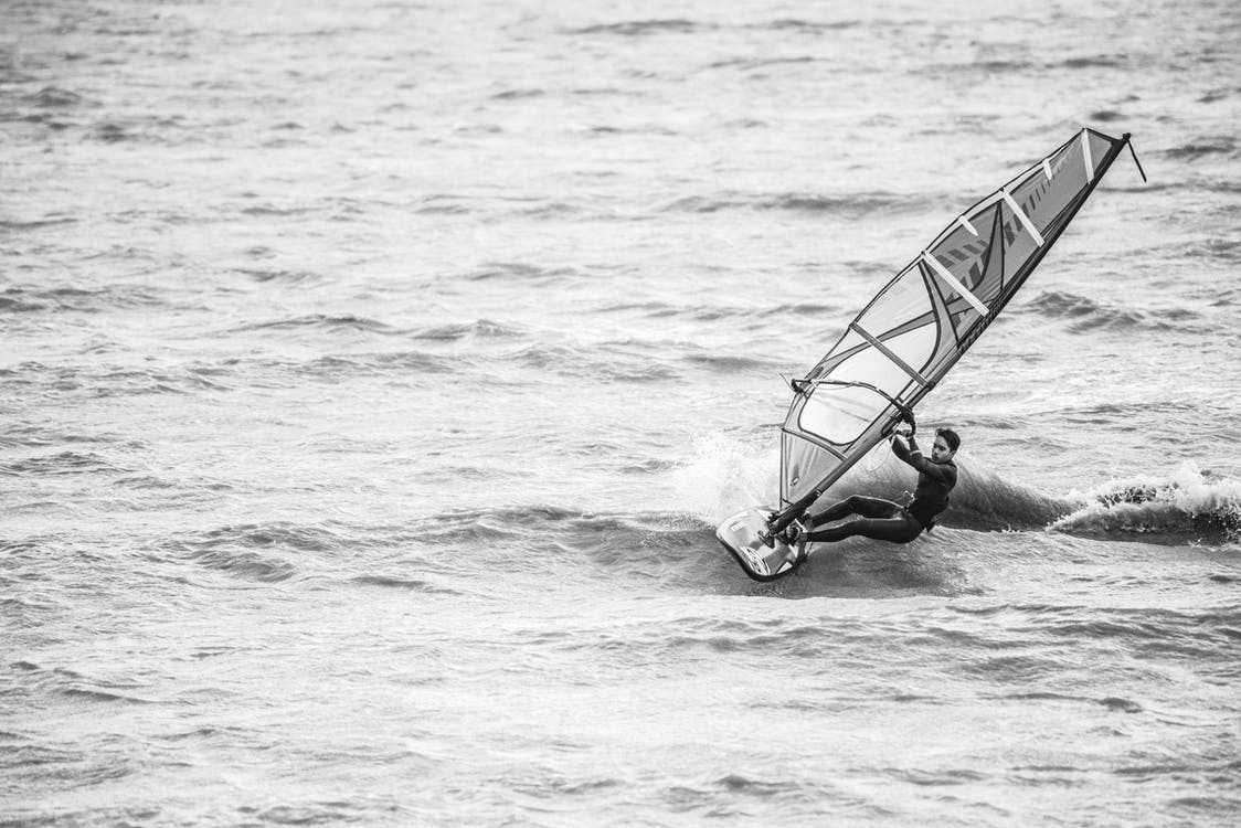 Grayscale Photography of Man Riding on Sailing Surf