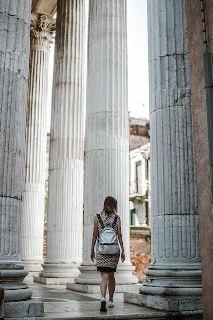 Woman walking through pillars of a building