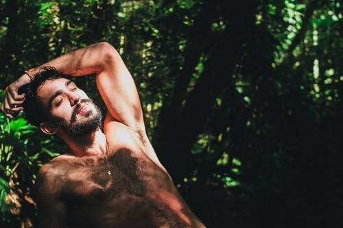 Photo of a Topless Man Surrounded by Plants