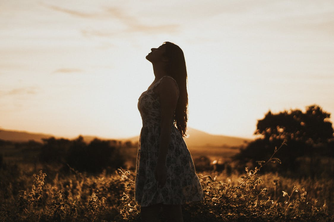 Photo Of Woman Standing In Field During Dawn