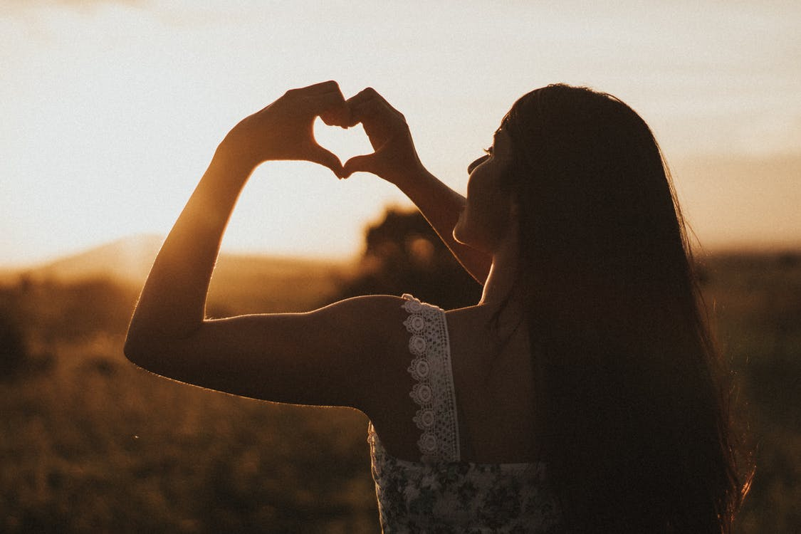 Shallow Focus Photo of Woman in White Thick Strap Top Showing Heart Hand Gesture