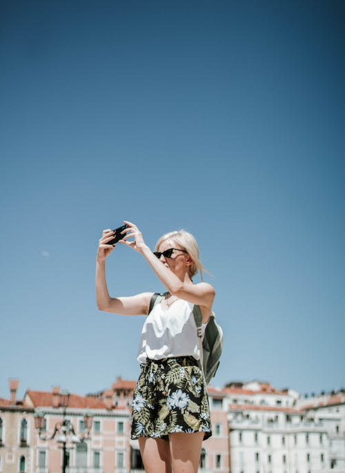Photo of Woman Wearing Black and White Floral Short and White Tank Top Taking Photo Using Black Smartphone
