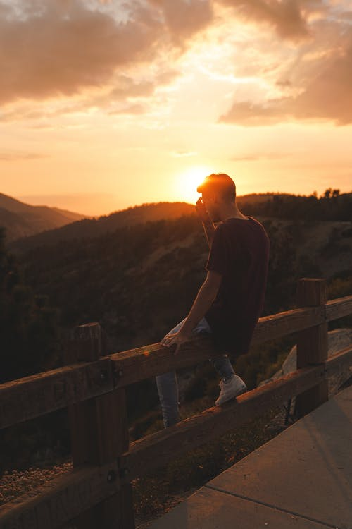 Photo Of Man Sitting On Wooden Fence During Dawn