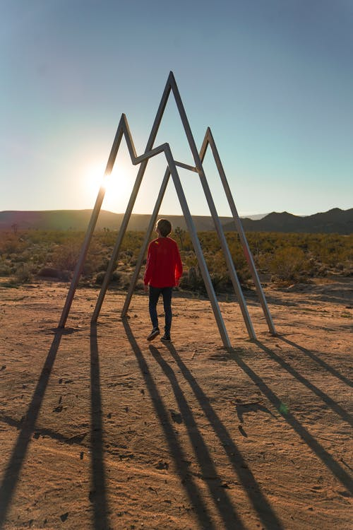 Boy Standing Under Triangular Frames