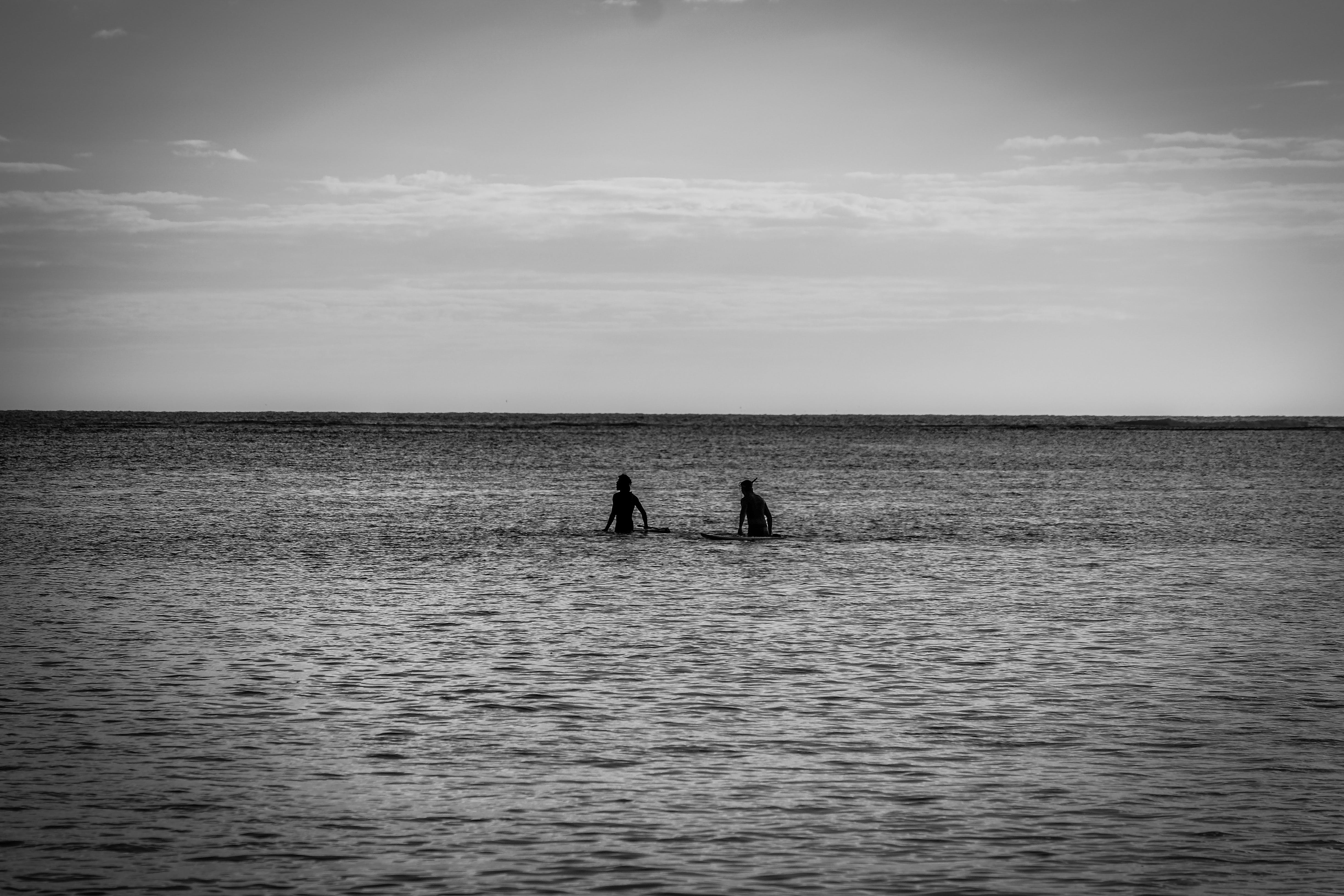 Grayscale Photography of Two Person in Body of Water