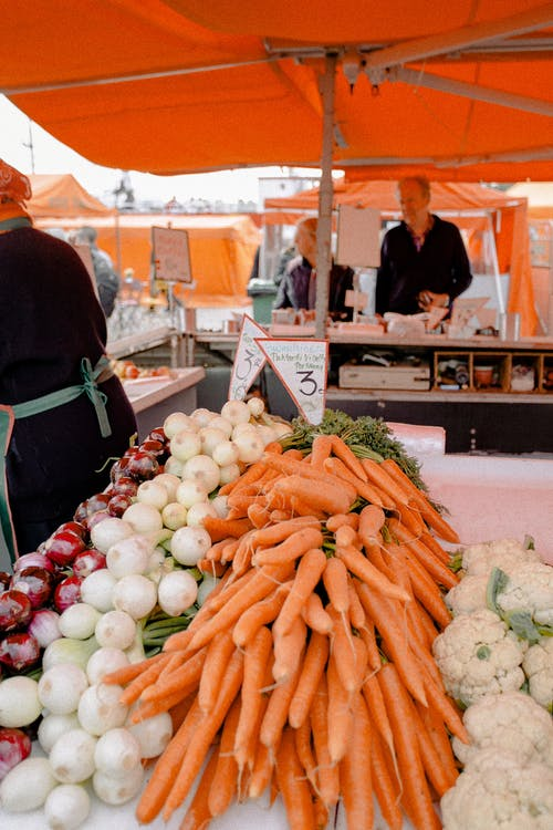 White and Orange Vegetables Under Orange Canopy