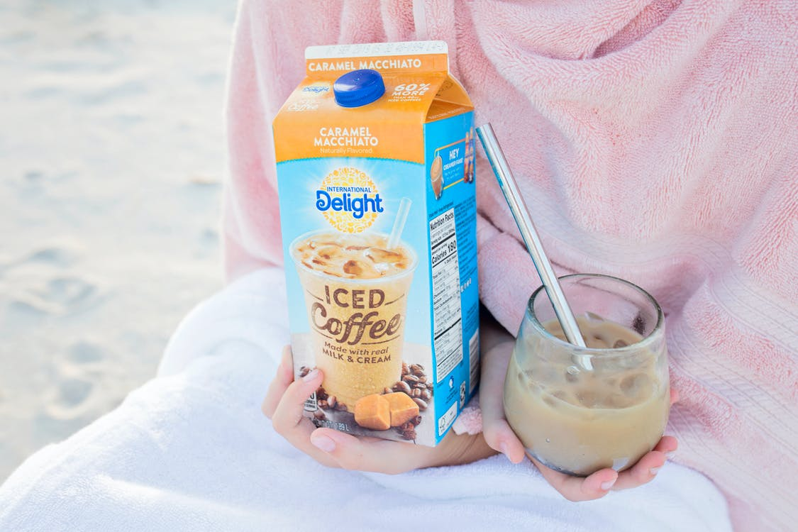 Person Holding a Carton and glass filled with Delight Iced Coffee