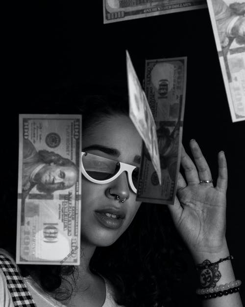 Grayscale Photography of a Woman Throwing 100 US Dollar Banknotes on Air