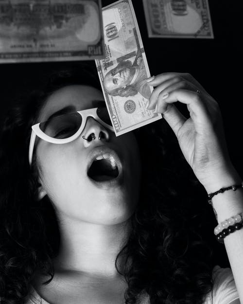 Woman Holding 100 US Dollar Banknote With her Mouth Open
