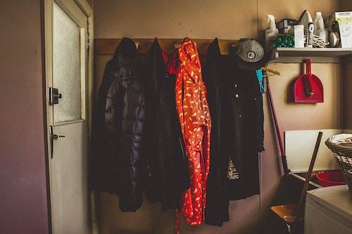 Hanged Black and Orange Coats Inside Room