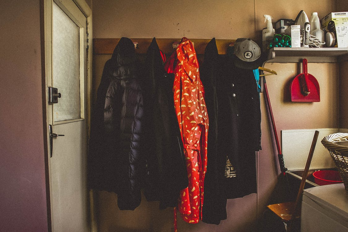Hanged Black and Orange Coats Inside Room