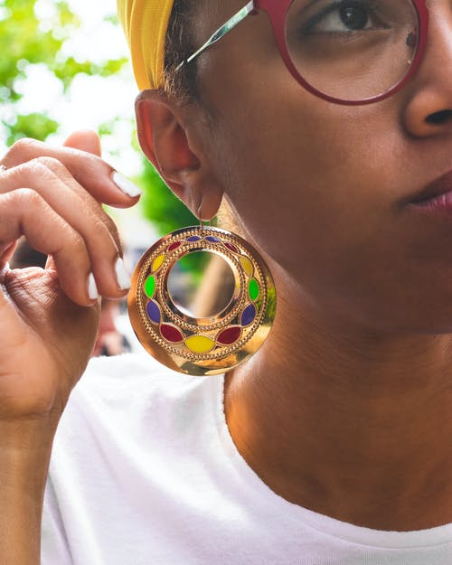 Selective Focus Photography of Woman Wearing Gold-colored Hoop Earring
