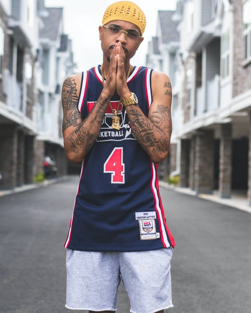 Selective Focus Photo of Tattooed Man in Basketball Jersey Posing