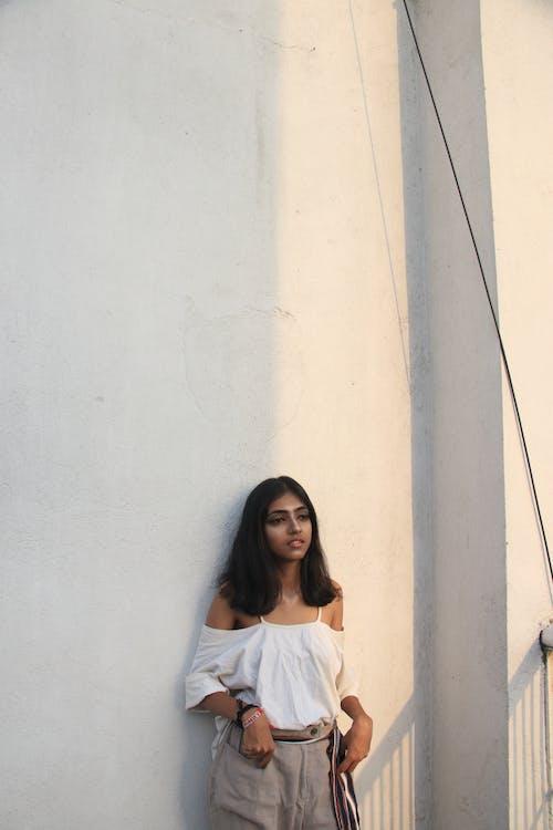 Foto profissional grátis de apoiando, de pé, mulher, muro