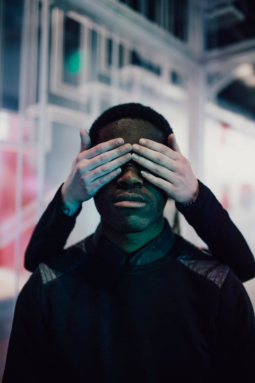 Portrait of a Person Covering eyes of a Man in Black  with her hands