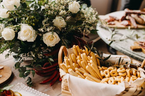 White-Petaled Flowers Beside Food On The Table