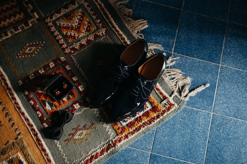 Pair of Black Leather Dress Shoes on Rug