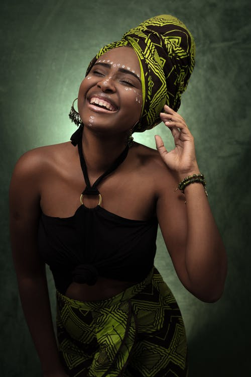Photo of Smiling Woman in African Headscarf and Skirt and Black Halter Top Laughing With Her Eyes Closed