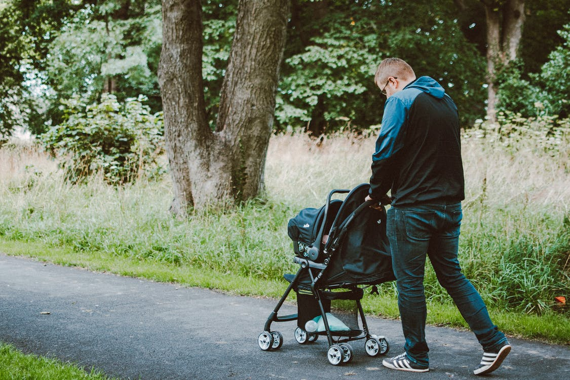Photo of Man Pushing Baby on Stroller on  Permeable Pavement