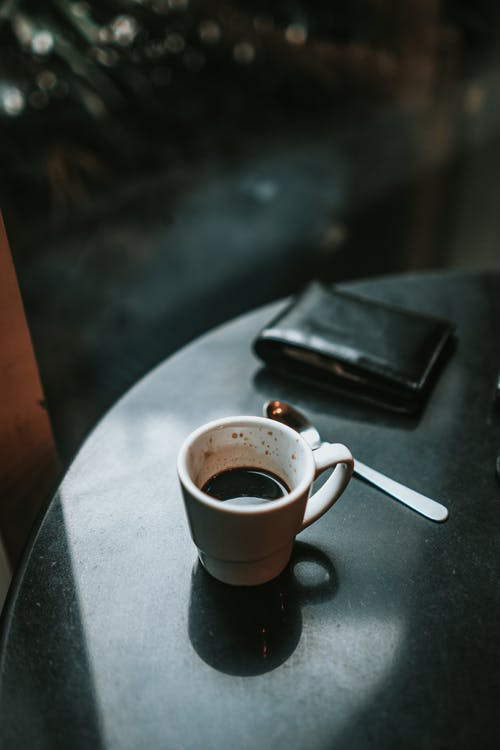 A Wallet and White Ceramic Mug Filled With Coffee on a table