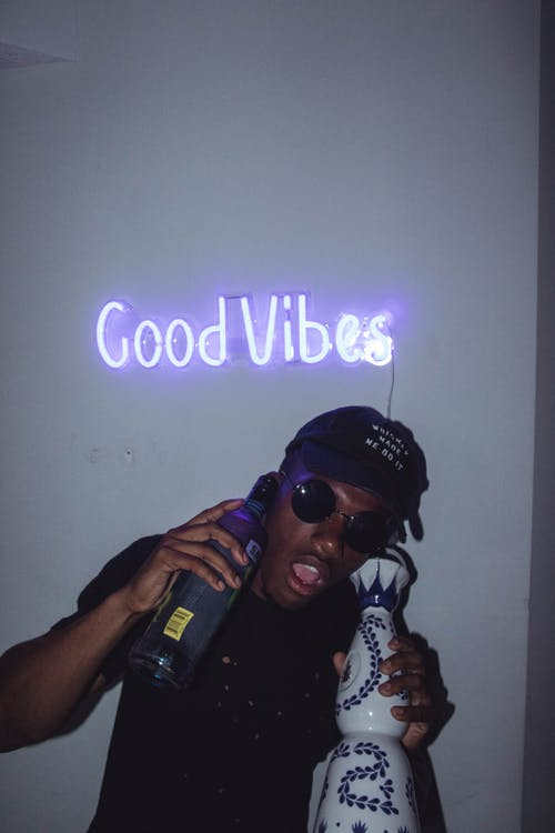 Man Wearing Black Cap Under Purple Good Vibes Neon Signage
