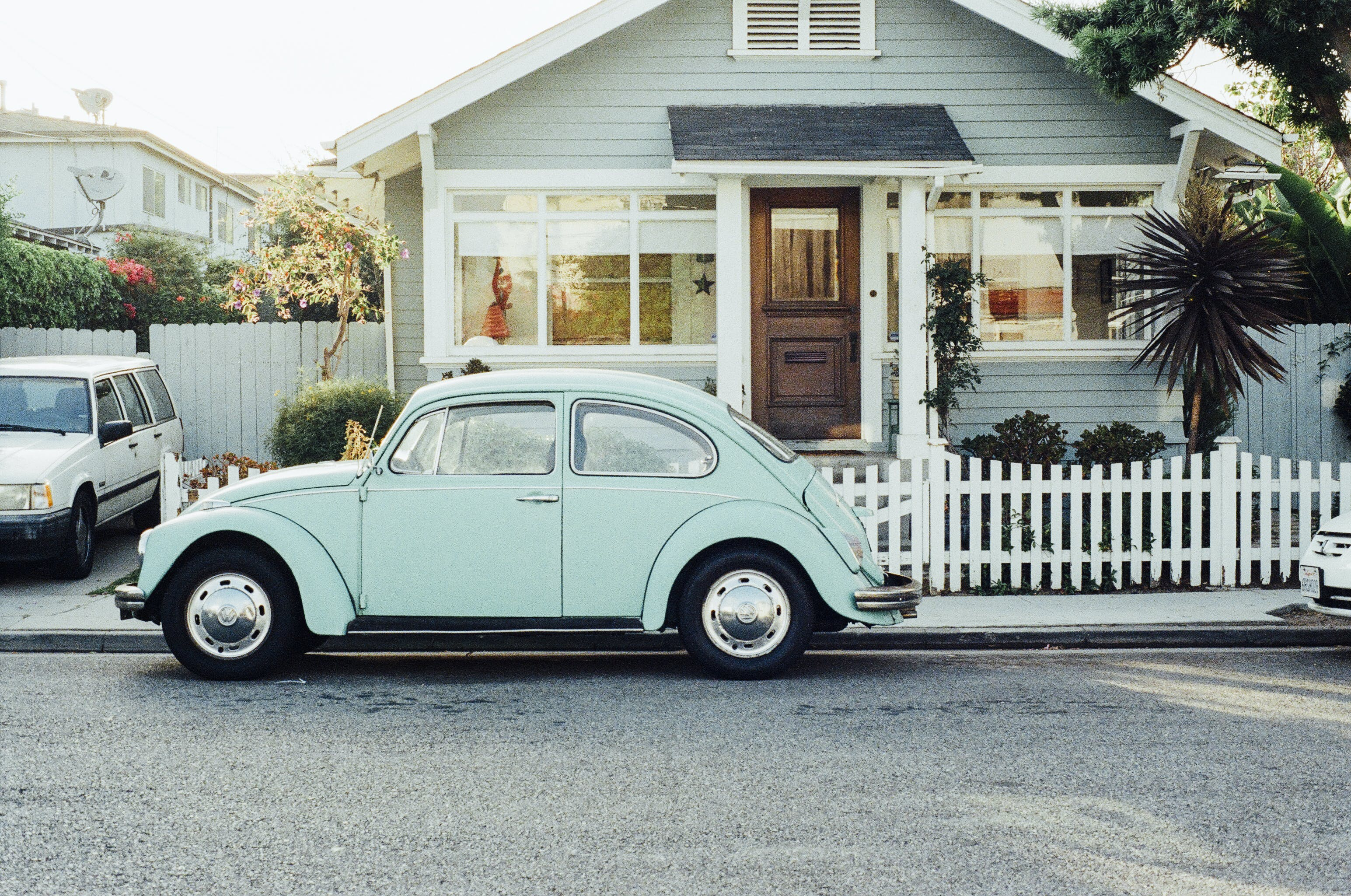 This is a photo of a light mint green old VW beetle car in front of a wodden house with a white fence in a residential area in a typical american street. There is a yucca palm tree in the lawn of the house. The sun is shining brightly.